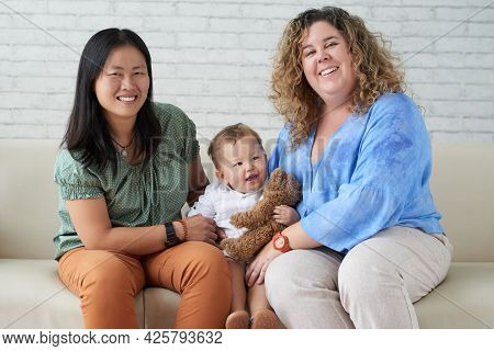Cheerful Married Lesbian Couple Playing With Their Baby Boy At Home