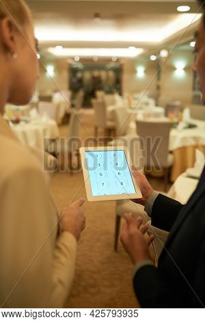 Banquet Manager Discussing Seating Plan On Tablet Computer With Restaurant Head Waiter