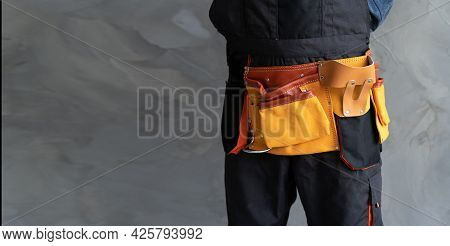 Close-up Of A Construction Belt At The Waist Of A Craftsman Standing Against A Gray Concrete Wall In