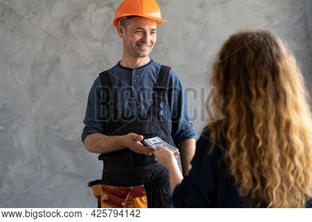 Woman Client Pays Man Construction Worker Repairman In Helmet Money Dollars In Hands Back View. The