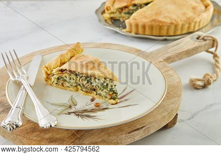 Slice Of Swiss Pie With Chard, Rice, Onions And Pine Nuts In Plate On Wooden Stand On White Marble