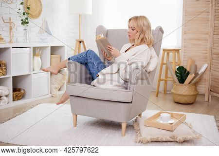 Young Woman Sitting On Armchair And Reading Book At Home