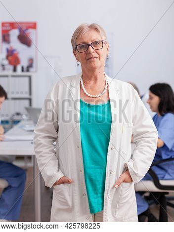 Portrait Of Senior Pediatrician Woman Standing In Front Of Camera Working In Conference Meeting Room