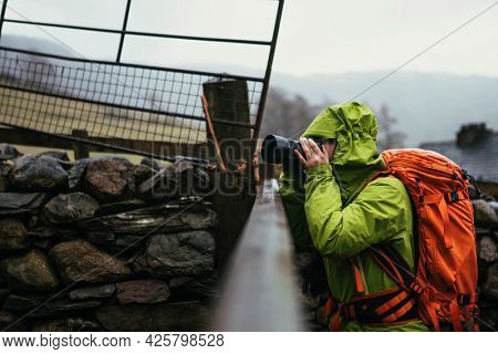 Photographer capturing the view over the fence