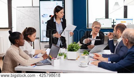 Woman Secretary Bringing Documents And Coffee To Executive Director While Multiethnic Team Planning