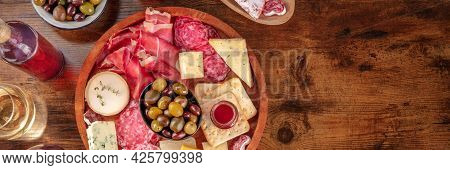Charcuterie And Cheese Platter With Wine And Olives Panorama, Shot From Above On A Dark Rustic Woode