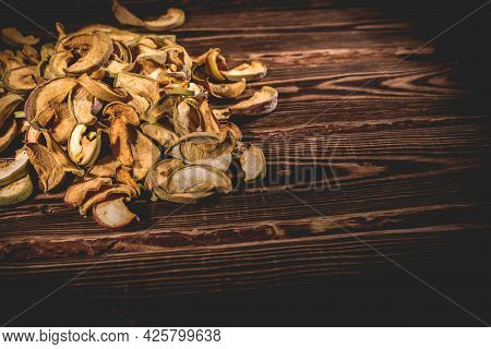 Slices Of Dried Apples On A Wooden Background. A Studio Photo With Hard Lighting.