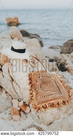 Straw hat and a woven bag on a rocky beach mobile phone wallpaper