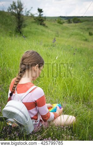 A Little Cute Girl Is Sitting On The Grass With A Pop It - Antistress Toy.