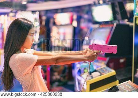 Arcade game machine adult woman shooting gun video games playing light shoot videogame virtual reality.