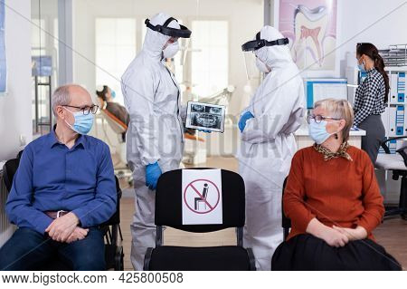 Man Discussing With Nurse In Dental Reception Wearing Protection Suit Against Coronavirus, Elderly P