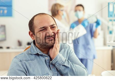 Man Patient Visiting Stomatology Cabient Complaining About Toothache During Orthodontic Appointment.