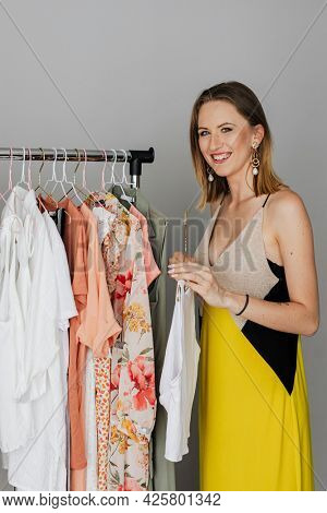 Cheerful woman in a yellow dress selecting cloth from a rack