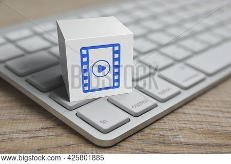 Play Button With Movie Flat Icon On White Block Cube With Modern Computer Keyboard On Wooden Table,