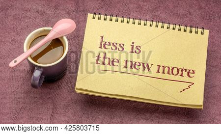 less is the new more - minimalism concept, handwriting in a spiral notebook with a cup of coffee