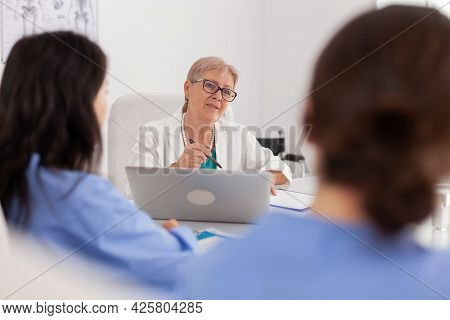 Portrait Of Physician Senior Woman Doctor Explaining Healthcare Medication Treatment Sitting At Desk