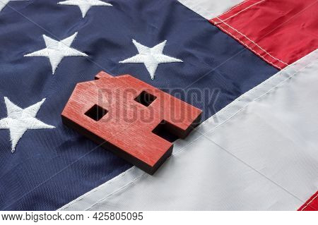 Va Streamline Refinance For Home Loan Concept. A Small House Lies On The American Flag.