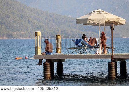 Hisaronu, Turkey - July 2021: People Sunbathing On A Beach On Green Mountains Background. Tourists