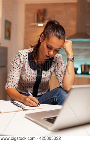Concentrated Freelance Woman Working Overtime To Finish A Project From Home Kitchen. Employee Using
