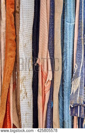 Colorful Pieces Of Old Dirty Rags Hang On A Rope As A Striped Background Extreme Closeup View