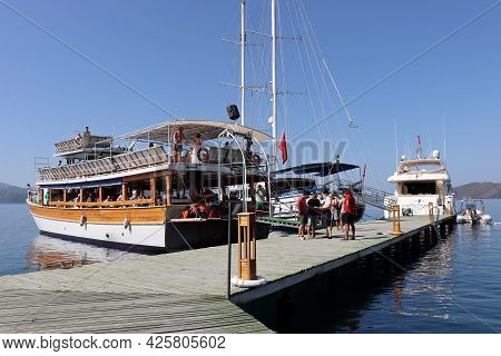 Hisaronu, Turkey - July 2021: Boat With Tourists Near The Wooden Pier In Aegean Sea. Summer Excurs