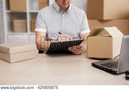Work, Business And Delivery Concept - Close Up Of Postman Hands Writing Something On The Clipboard I
