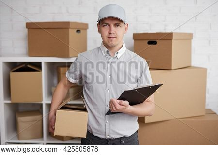 Postal Delivery Concept - Young Man Worker In Uniform Posing In Warehouse With Box And Clipboard