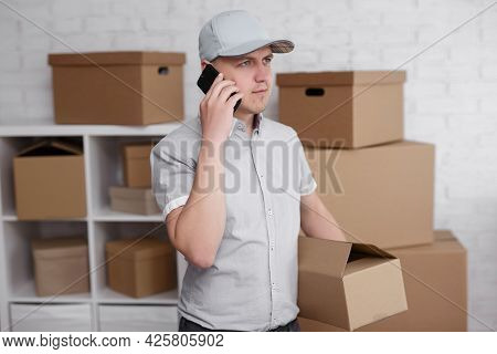 Postal Delivery And Business People Concept - Man In Warehouse Calling By Phone With Box In Hand