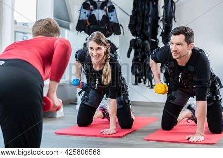 Woman and man with trainer in ems gym doing triceps exercise