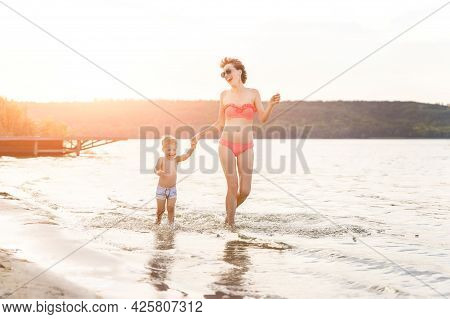 Young Adult Attractive Slim Sporty Mother Enjoy Having Fun Running Water By Lake Or Sea Sand Breach
