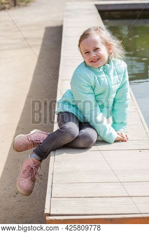 Lonely Little Caucasian Girl Sitting By The Lake Water And Looking At The Camera. Water Surface Of T