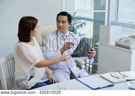 Physician Discussing X-ray Of Feet With Female Patient And Discussing Upcoming Surgery