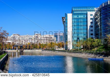 Bucharest, Romania, 22 November 2020: Landscape With Dambovita River, Old Buildings And Yellow, Oran