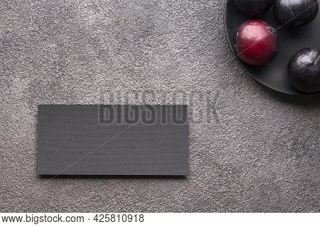 Business Card Invitation Black Postcard On Gray Concrete. Flat Lay Plums, Dark Key. A Stylish Invita