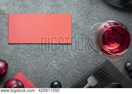 A Glass Of Wine And A Red Postcard On A Gray Concrete Table. An Invitation To A Restaurant For A Cel