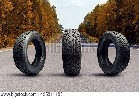 Three Winter Tires On An Autumn Road. Upcoming Seasonal Tire Replacement