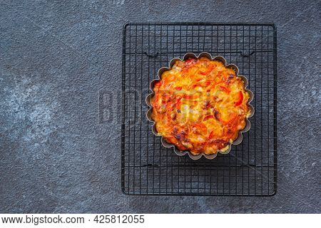 Unsweetened Pie Or Mini Tart With Egg, Chicken, Bell Pepper And Cheese On A Black Wire Rack On A Bla
