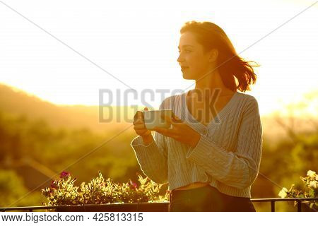 Confident Woman Holding Coffee Cup Contemplating At Sunset In A Balcony