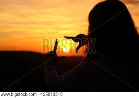 Backlight Portrait Of A Woman Hands Silhouette Framing Sun At Sunset