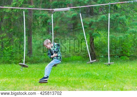 A Boy Overcomes Obstacles In A Rope Track In The Forest In Summer Or Spring.