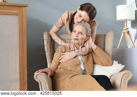 Happy Daughter Hugging Older Mother, Standing Behind Chair In Living Room, Enjoying Tender Moment At