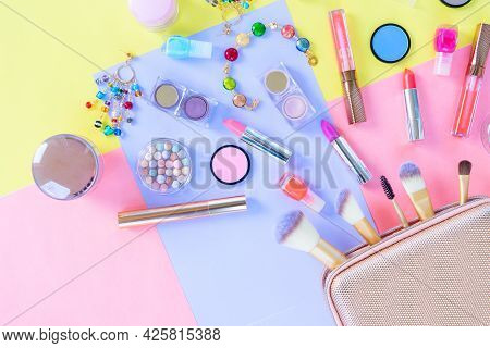 Colorful Scattered Make Up Products With Golden Pursue On Plain Color Block Background