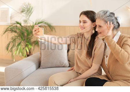 Happy Middle Aged Mother And Daughter Taking Selfie At Home.