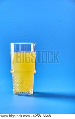 Orange Juice In Glass On Blue Background. Refreshing Summer Drink. Copy Space For Your Text. Vertica