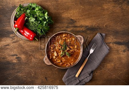 Traditional Goulash Meat In Ceramic Bowl With Pepper And Herbs, Fork And Napkin. Top View, Copy Spac