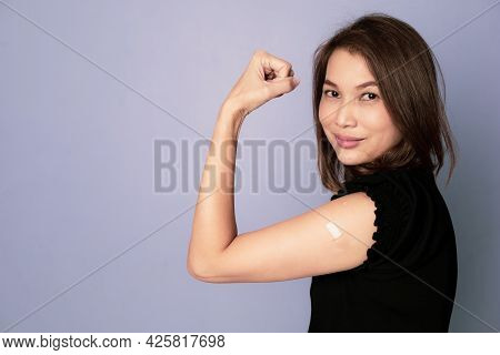 Portrait Of Vaccinated Asian Woman Showing Plaster Band Aid On Arm And Show Fist Punch In Winning An