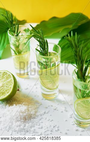 Summer Alcoholic Cocktail. Refreshment Lemon Soda Drink. Gin And Tonic With Lime And Rosemary On Yel