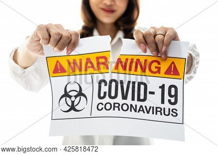 Woman Holding And Tearing Paper With Covid-19 Coronavirus Warning Words. The Idea Or Concept For The
