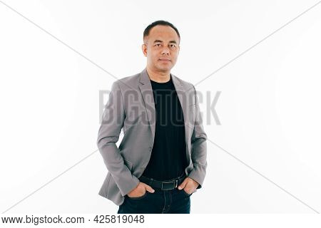 Portrait Of Self-confident Middle Age Senior Asian Man In A Black T-shirt And Grey Jacket. Isolate O