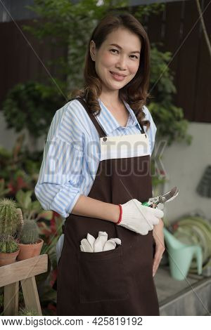 Cute Asian Housewife Wearing Apron Holding Pruning Shears Cross Hands And Looking To Camera Ready To